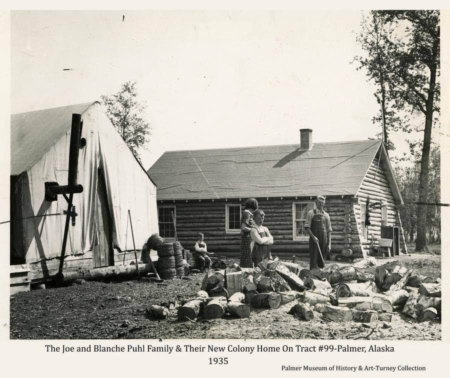 This is a press photo exhibiting marks indicating where it was cropped for publication in the newspaper.  Image is a summer view of Joe and Blanche Puhl and their two sons at a wood pile next to their Colony tent and their new log home on farm tract #99 on the north side of Palmer.  Rolls of barbed wire are stacked by the tent and blocks of birch wood await in the foreground to be split for fire wood.