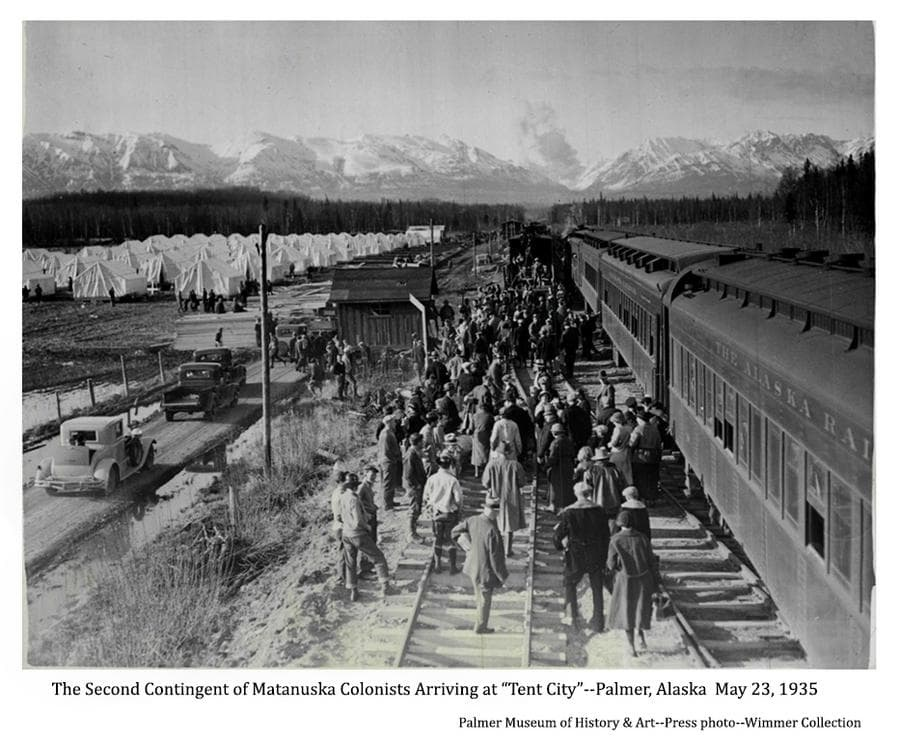 The image shows a group of people, identified as the second contingent of Matanuska Colonists from Michigan & Wisconsin, walking beside railroad cars toward white tents in the middle ground.  Pickup trucks and cars are at left, a small building is in near middle ground and the train depot is visible in far middle ground.  Forest is in far middle ground with snow-clad Talkeetna Mountains in background.