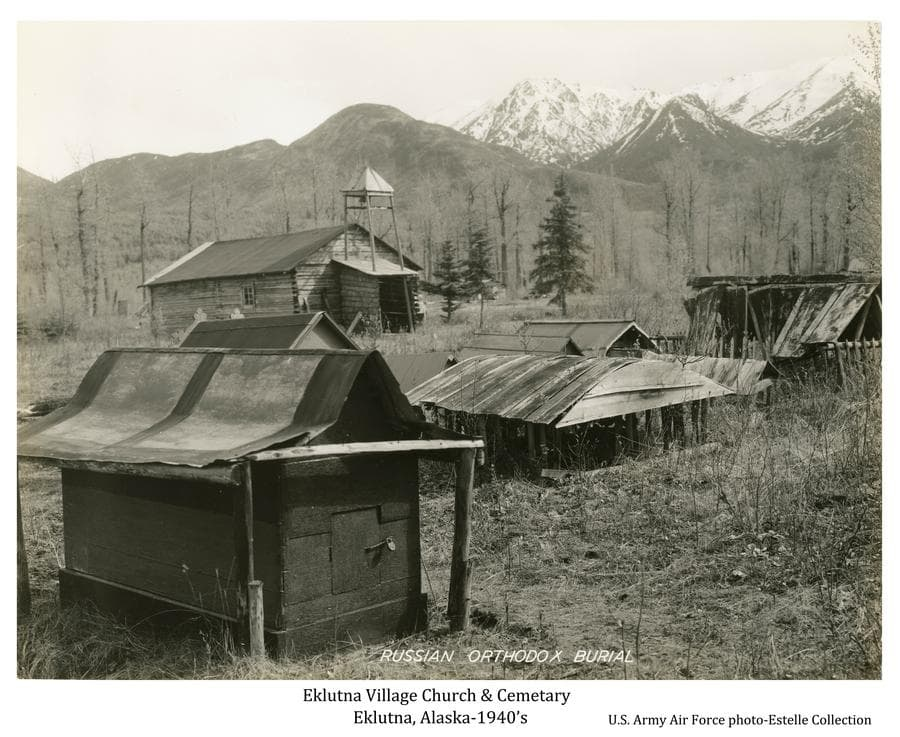 Image shows a springtime view of several Native burial houses in foreground, a log Russian Orthodox church in middle ground, trees and snow-clad mountains beyond.