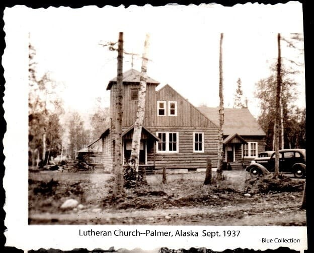 Image shows the front of the Lutheran church in Palmer surrounded by trees. Two cars are parked in front of the church.