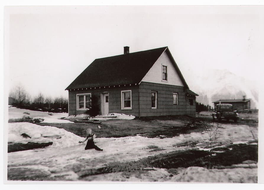 Image is an early spring view of a house with snow patches in the yard. A small boy is playing in the snow. A pickup truck is parked next to the house, an outbuilding is in the middle ground with trees and snow-clad Pioneer Peak beyond. This appears to be a later view of House#4.