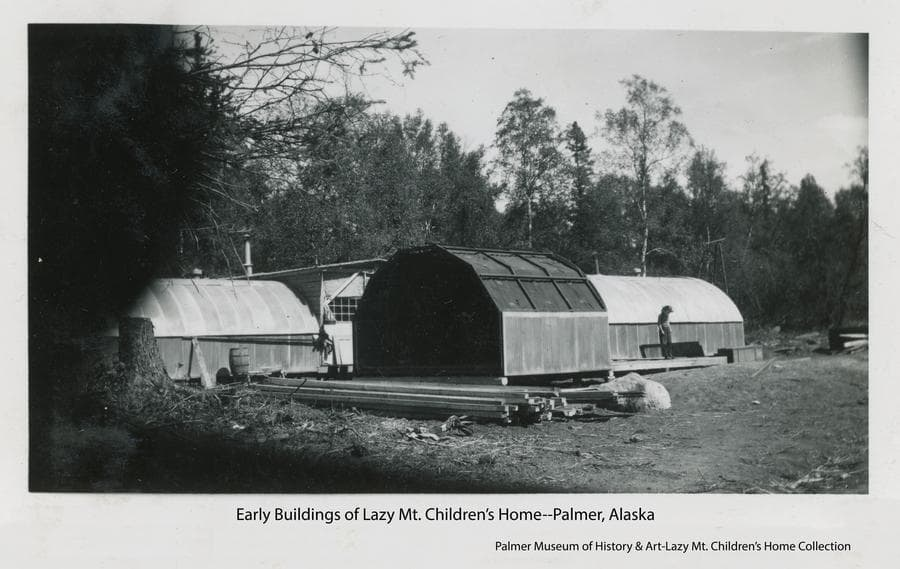 Image shows two Quonset Huts connected by a frame structure in middle ground with heavy forest behind.  Another smaller hut section without roofing is in foreground with a pile of lumber next to it.  A child stands nearby on a wood deck.
