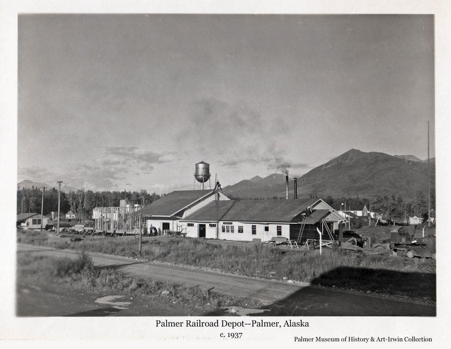 Image is a summer view of the west side of the Palmer Railroad Depot.  Construction is continuing on expanding the warehouse at the north end of the building and on the small addition at the south end.  The water tower is evident as are portions of other Co-op buildings.  Lazy Mt. and other mountains are in background.