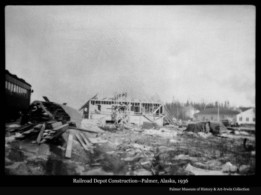 Image is a winter view of the Palmer Railroad Depot under construction with the wall framing in place and long boards leaning up against the walls on both sides.  A pile of lumber is in foreground, a rail car is in foreground at left, the co-op garage is visible at right.