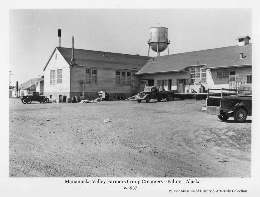 Image is a summer view of the Matanuska Valley Farmer's Co-op Creamery building in Palmer with three vehicles in front.  The water tower is visible behind and the powerhouse is partially visible at left.