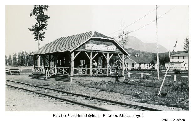 Image shows railroad tracks in foreground and an adjacent open-sided roofed building with a sign on it identifying EKLUTNA. A person is visible inside the building. Large white buildings of the Eklutna Vocational School are in middle ground. A cottonwood tree is obvious next to the foreground building. Forest and mountains in background. Power lines are evident overhead.