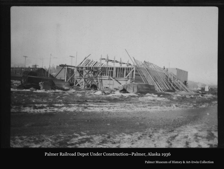 Image is a winter view of the Palmer Railroad Depot under construction with the wall framing in place and long boards leaning up against the walls on both sides.  Portions of other buildings are visible.
