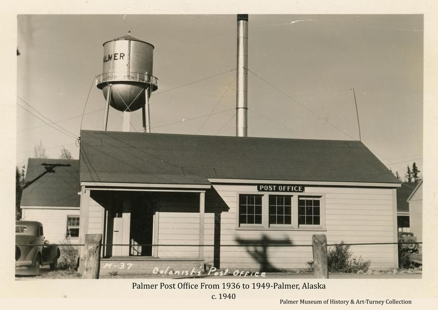 Image is a view of the front of the new Post Office building constructed as part of the Matanuska Colony project in front of the powerhouse on what was to become Dahlia Ave.   The water tower is prominent and a portion of the powerhouse and its smokestack are visible behind.  A cable and post hitching rail is in foreground and two automobiles are partially visible.  Postal service moved from Jim Felton's store to this facility in 1936 where it operated until 1949.  This postcard photo is estimated to have been taken about 1940.