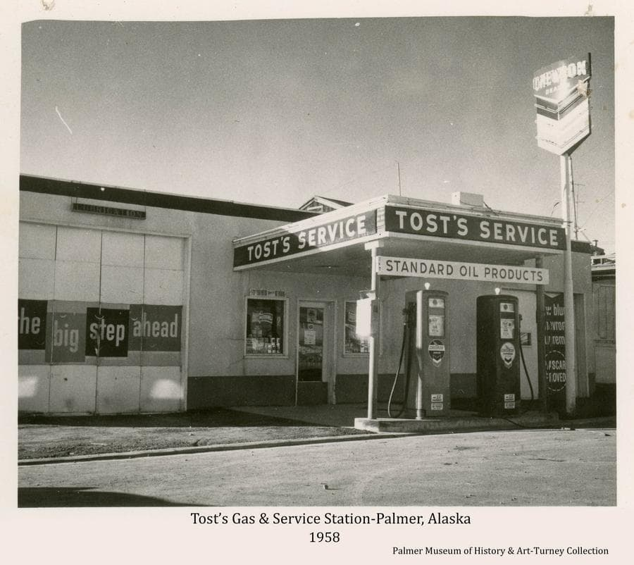 Image is of the east face street view of Tost's Service Station building in downtown Palmer as it appeared in fall of 1958.  Signs are evident advertising Standard Oil products and Chevron gasoline.  The street in front is newly paved.