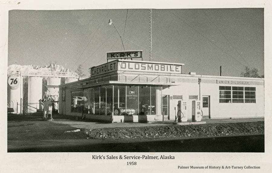 """Image is the street view of the north and west facing sides of Kirk's Sales & Service Station building in Palmer as it appeared in fall of 1958.  Signs are evident advertising Chevrolet and Oldsmobile automobiles and Union Oil products.  Gas pumps are visible in front of both sides of the building.  Bulk fuel tanks are evident behind the building exhibiting a large """"76"""" sign. The street in front is newly paved."""