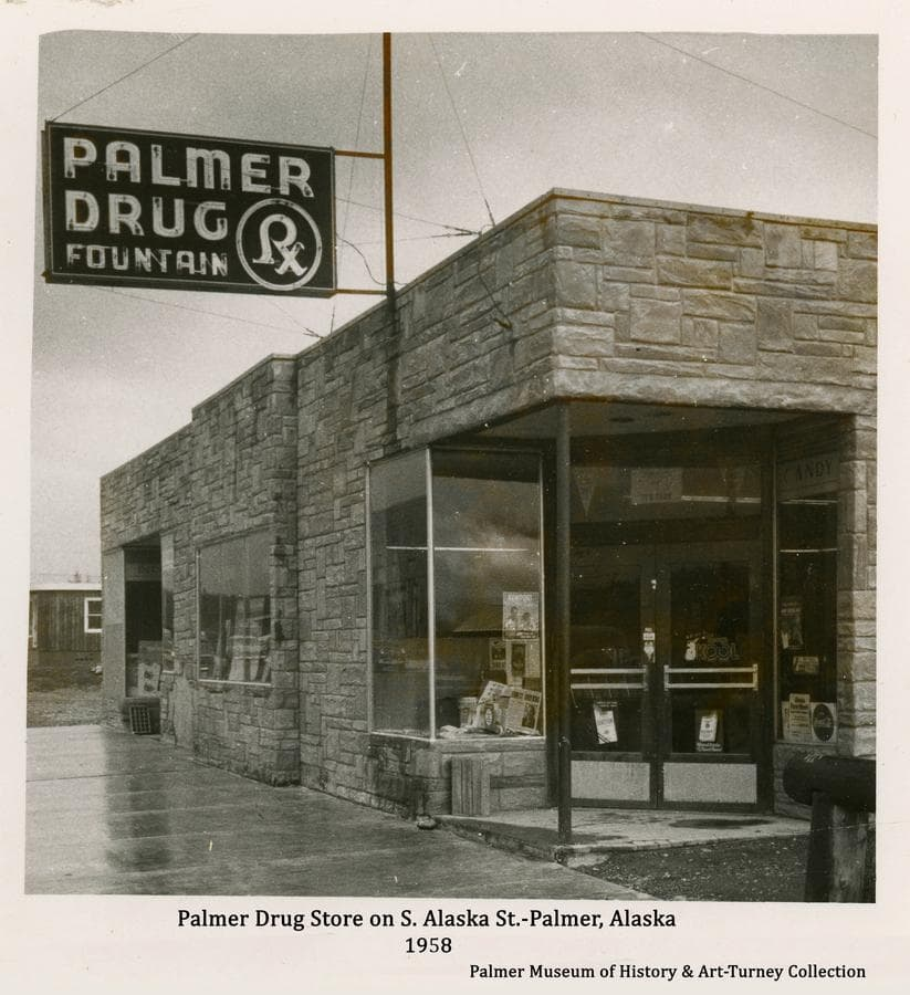 Image is of the southwest entry and west side of the Palmer Drug Store on South Alaska Street in Palmer as it appeared in fall of 1958.  The new sidewalk associated with the recently paved street is evident.   The Palmer Drug Fountain sign is prominent.