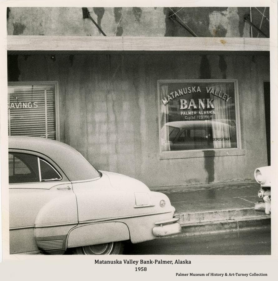 """Image is a street-side view from S. Colony Way of the sidewalk and building window advertising the """"Matanuska Valley Bank"""" and partial view of another window advertising """"Savings"""".  Two cars are parallel parked in front at the curb of the newly paved street."""