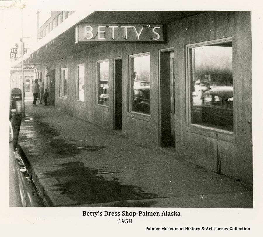 """Image is a view of the front of Betty's Dress Shop on S. Valley Way.  A neon sign, """"BETTY'S"""" is prominent under the canopy covering the new sidewalk associated with recent street paving activity carried out by the city in 1958."""