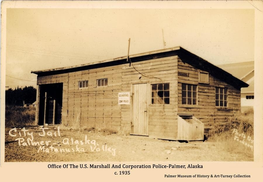 """Image is a view of a shed-roofed building with three nine-pane windows and two small high windows that appear to have bars.  A sign at the entrance identifies it as headquarters for the U.S. Marshall and Corporation Police.  The photographer's note on the front of the print indicate it was the Palmer """"City Jail"""".  It appears to be a temporary and hastily constructed facility in the early days of the Matanuska Colony project in Palmer."""