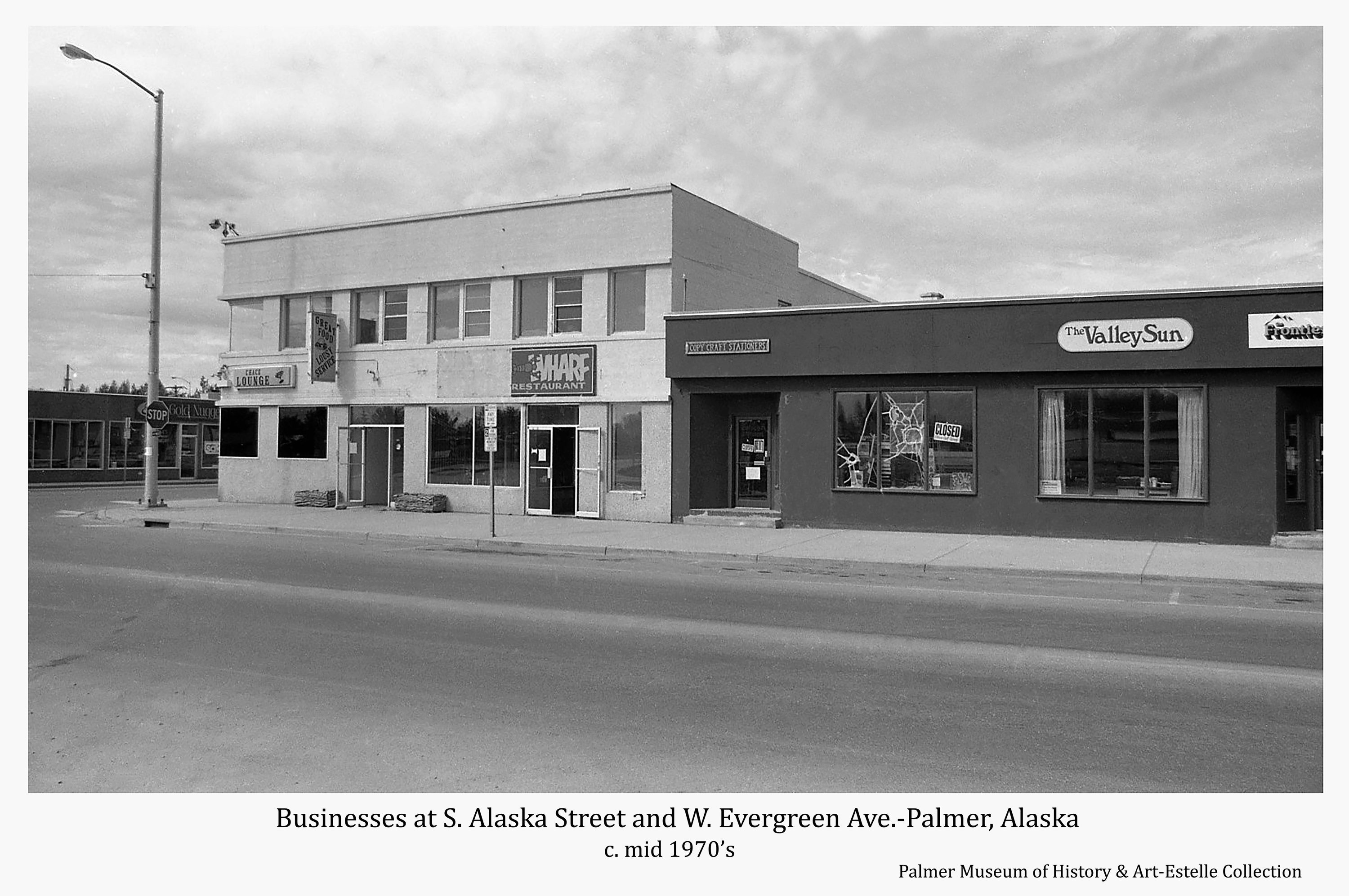 Image is a street view of businesses on the west side of South Alaska Way located between West Evergreen and West Dahlia Avenues and a partial view of a building on the south side of West Evergreen Ave.  A sign identifies a business shown as The Gold Nugget… south of West Evergreen.  Fronting on South Alaska Street are the Chase Lounge, The Warf Restaurant, City Craft Station, The Valley Sun, and Valley Frontiersman.