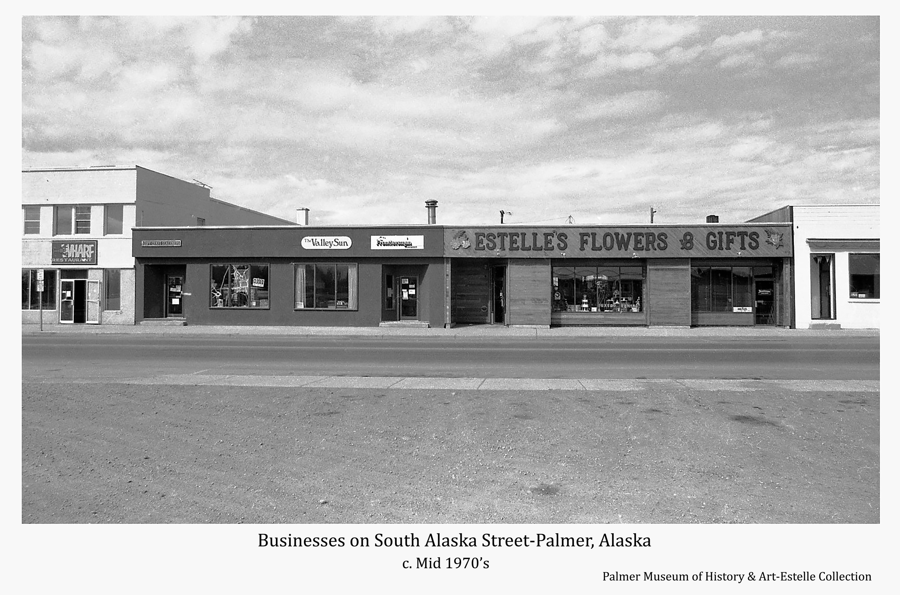 Image is a street view of businesses on the west side of South Alaska Way located between West Evergreen and West Dahlia Avenues.  Signs identify businesses shown as The Warf Restaurant, City Craft Station, The Valley Sun, Valley Frontiersman, and Estelle's Flowers and Gifts.  Part of the building occupied at the time by Allen & Peterson is visible at right.