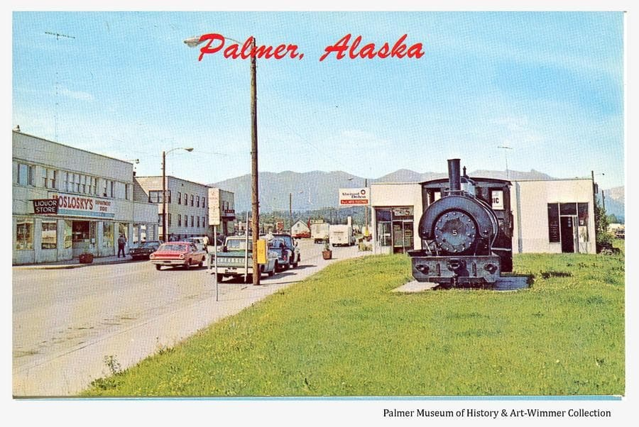 This is a color postcard image looking north along S. Alaska St. with Koslosky's department store and the Valley Hotel evident on the left.  The building across the street from Koslosky's, originally the Palmer Drugstore, exhibits a sign indicating it was occupied by B&C Auto Electric at the time the photo was taken.  Railroad engine #5 sits on the green between S. Alaska and S. Valley Way in foreground.