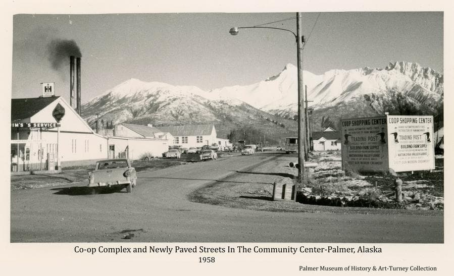 Image is an easterly view at the intersection of South Valley Way and Dahlia Ave. in Palmer as it appeared in fall of 1958.  Buildings of the Co-op are evident at left and signs are visible.  Automobiles are evident. Snow-clad mountains are prominent in background.  The included streets are newly paved.
