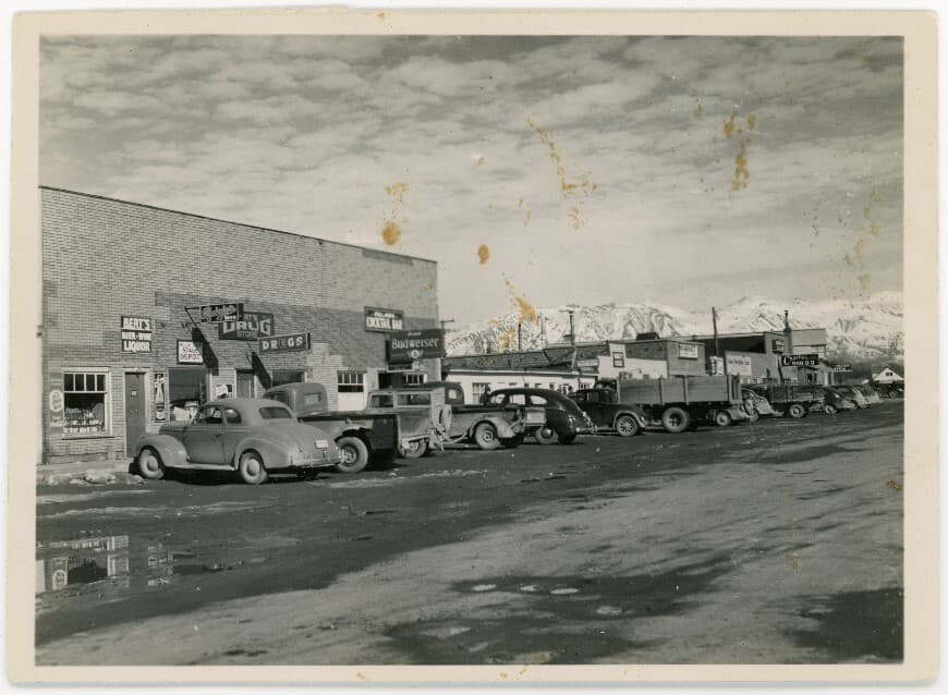 Image is a street scene of downtown Palmer businesses with vehicles parked in front. Numerous signs are evident and a variety of vehicles. Gravel street in foreground, snow-clad mountains in background.