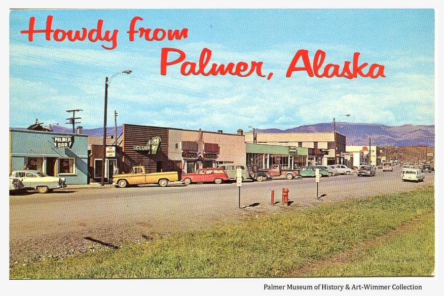 This is a summer color postcard image of businesses along S. Colony Way in downtown Palmer.  Some buildings on S. Alaska Street are also visible.  Numerous automobiles are parked along the street and several business signs are evident.  Talkeetna Mountains are visible in background.