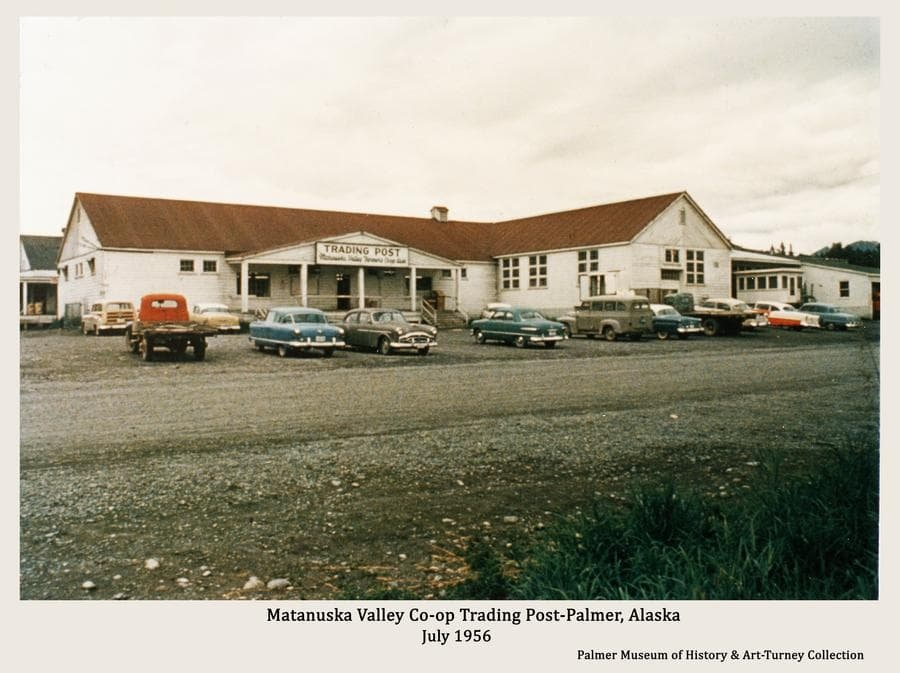 Image is a summer street-side color view from Dahlia Ave. of the Co-op Trading Post and Creamery building with numerous automobiles parked in front.  The warehouse behind the store is partially visible.