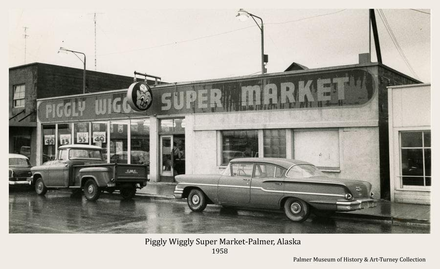 Image is of the Piggly Wiggly Super Market facing onto South Colony Way in Palmer as it appeared in fall of 1958.   Automobiles are parked in front and signs are evident.  The street is newly paved.