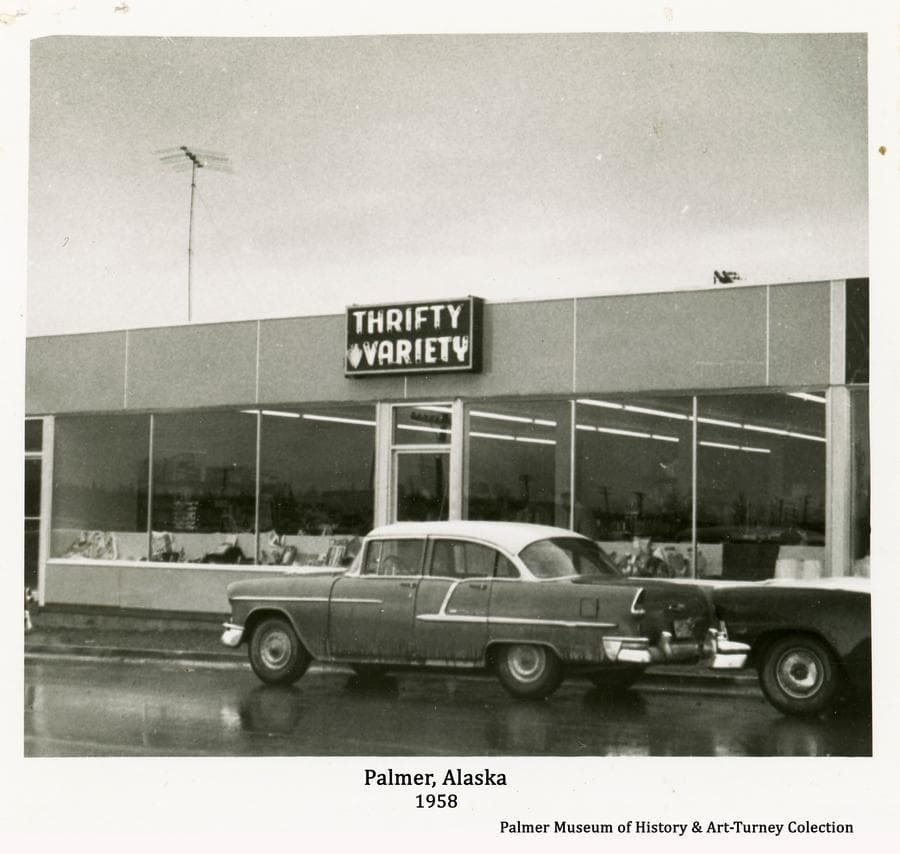 Image is of the Thrifty Variety Store facing onto South Colony Way in Palmer as it appeared in fall of 1958.   Automobiles are parked in front and signs are evident.  The street is newly paved.
