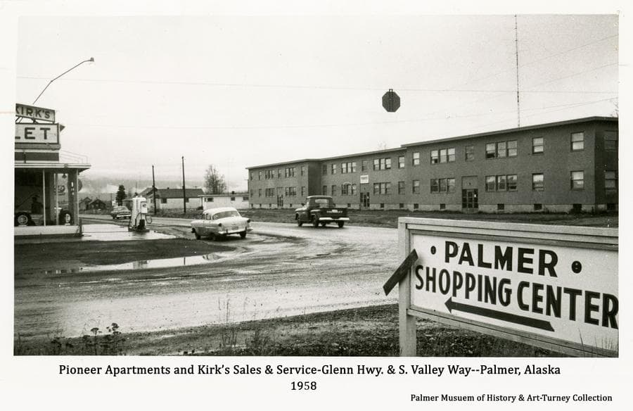 """Image is a view of Pioneer Apartments and Kirk's Sales & Service at the intersection of Glenn Highway and S. Valley Way.  A sign is prominent in foreground with an arrow pointing to """"Palmer Shopping Center"""".  New pavement on S. Valley Way is evident as part of the city street paving project of 1958.  Three vehicles are evident."""