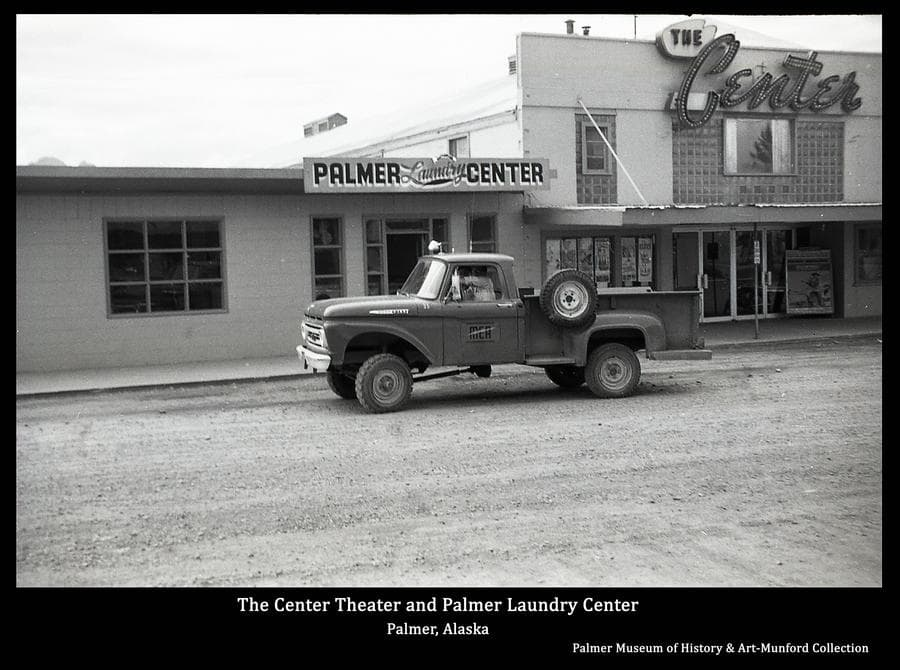 """Image is a summer street view of the entrance to Center Theater and the Palmer Laundry Center.  A pickup truck with a MEA logo on the door is in front of the buildings.  """"The Center"""" and """"Palmer Laundry Center"""" signs are evident."""