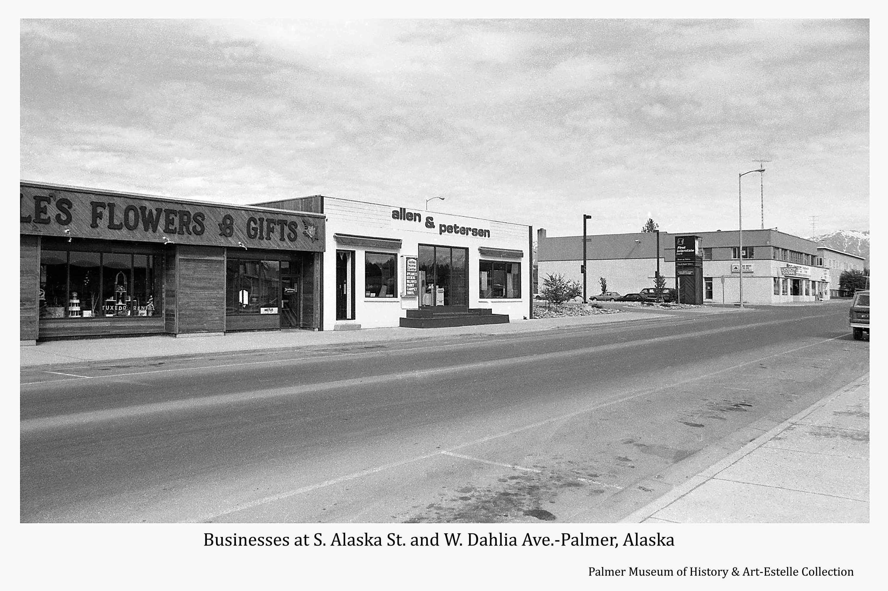 Image is a street view of businesses on the west side of South Alaska Way located between West Evergreen and West Dahlia Avenues and on the north side of West Dahlia Avenue.  Signs identify businesses as Estelle's Flowers & Gifts, Allen & Peterson, First Interstate Bank, and Koslosky's Department Store containing an Insurance office and a Liquor Store.  A portion of the Valley Hotel is also visible.