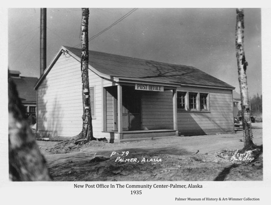"""Image is of the front of the newly constructed Post Office in the Community Center of Palmer.  In foreground is a rough roadway that will become called """"Market Street"""" for a time and later designated as Dahlia Ave.  The powerhouse is partially visible behind the Post Office.  Two lonely and abused birch trees continue to stand in the foreground."""