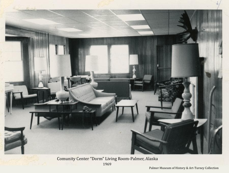 """The Community Center Dormitory was initially built to provide housing for single teachers, nurses and others during the early days of the Colony.  It later provided public hotel rooms under private ownership.  The accommodations included a community """"living room"""" with a fireplace and space for small gatherings.  This image shows how that room was furnished in 1969."""