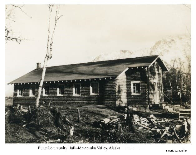 Image shows the north side of the log Butte Community Hall with lumber and clearing debris in foreground and Pioneer Peak in background.