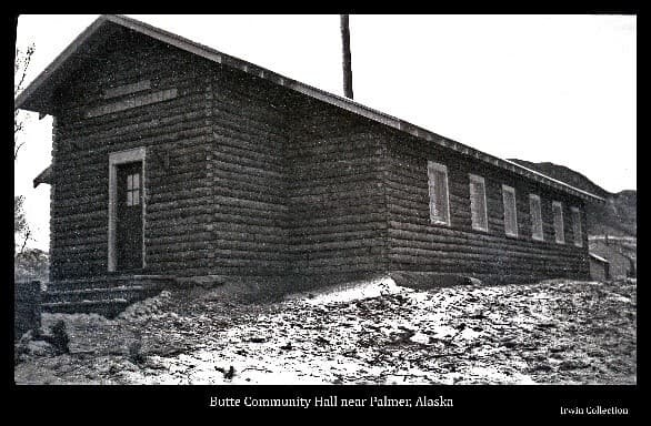 Image shows the front and south side of the log community hall constructed soon afer the Matanuska Colonists settled the area around the Bodenburg Butte. A portion of the Butte is visible behind the building as is one of the typical colony tents.