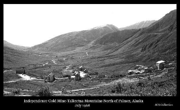 Image is a southerly view of a mountain valley containing numerous buildings associated with the Independence Gold Mine. Several vehicles are visible. A small stream is evident as are roads leading up to the mine and to Hatcher Pass on the right. The photo was taken from the area developed for skiing at the time.