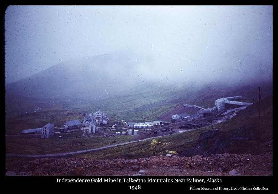 Photo is a color view of the buildings of Independence gold mine taken from the north above as it appeared in 1948.  The view includes bunkhouses and administration buildings, fuel tanks, ore processing buildings and mine timber piles.
