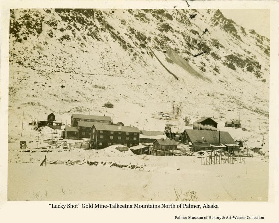 """Image is a winter view of the """"Lucky Shot"""" gold mine in the Craigie Creek drainage of the Talkeetna Mountains north of Willow, Alaska.  Shown are the buildings of the mine complex at the base of the mountains and tailings from the lower Lucky Shot adit on the mountainside above."""