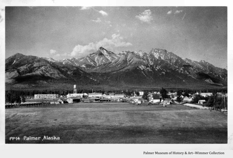 Image is a summer view looking east from Bugge's Hill showing John Bugge's homestead field and buildings, the buildings of Palmer, and mountains including Lazy Mt. and Beyers Pk. in background.