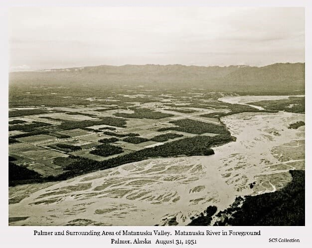 Image is an oblique aerial view looking northwest across the Matanuska Valley with the braided channel of Matanuska River in foreground. The City of Palmer, Palmer Airport, and surrounding farms are evident beyond the river. Land clearing patterns are apparent. Talkeetna Mountains are in background.