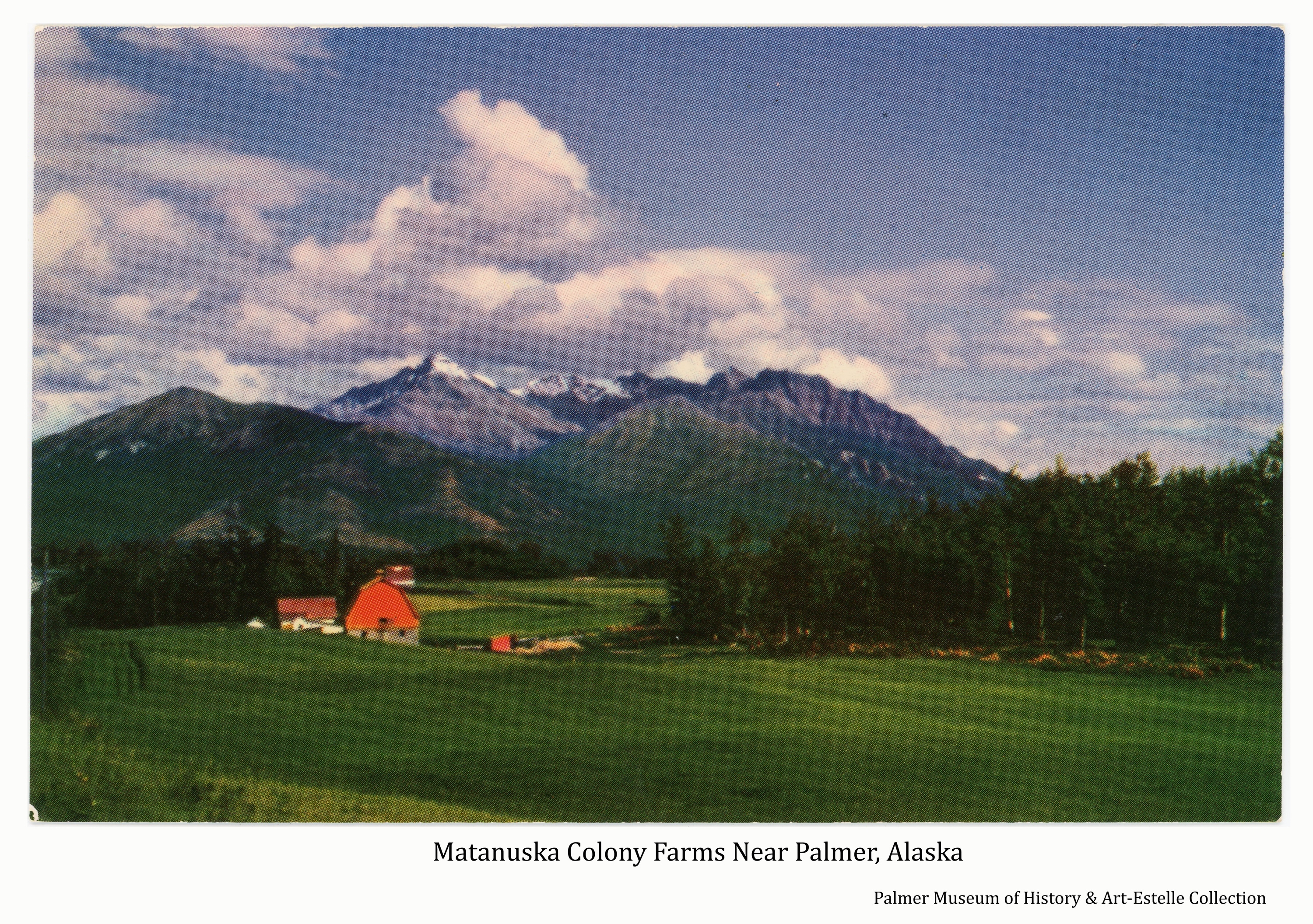 Image is a late summer easterly view of a green hay field in foreground with an orange Colony barn and other farm buildings on Colony tract #169 in middle ground.  Another Colony barn on tract #112 is visible beyond.  Patches of uncut forest are apparent.  Lazy Mountain and Beyers Peak, dusted with new snow, are in background with clouds overhead.