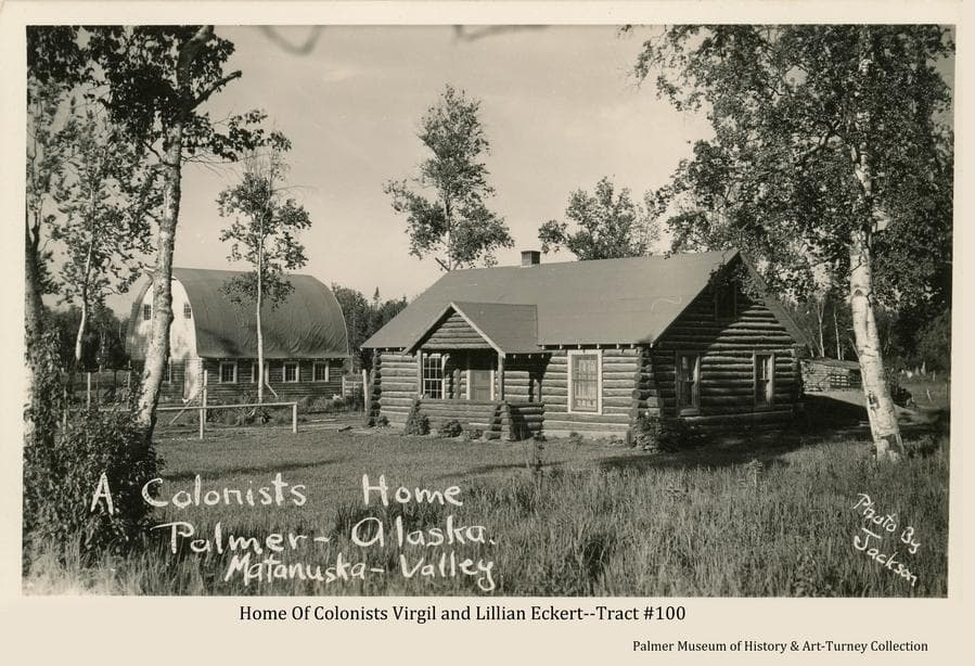 """Image is a summer view of the Colony home and barn of Virgil and Lillian Eckert on their farm tract #100 on the north edge of Palmer.  The house is of the log """"cabin"""" style as were many of the Colony homes.  The round-roofed barn was not typical of the Colony barns and was one of only three or four constructed of that style.  A smaller log building is visible behind the house.  Scattered birch trees are around the farmstead with heavy birch forest beyond."""