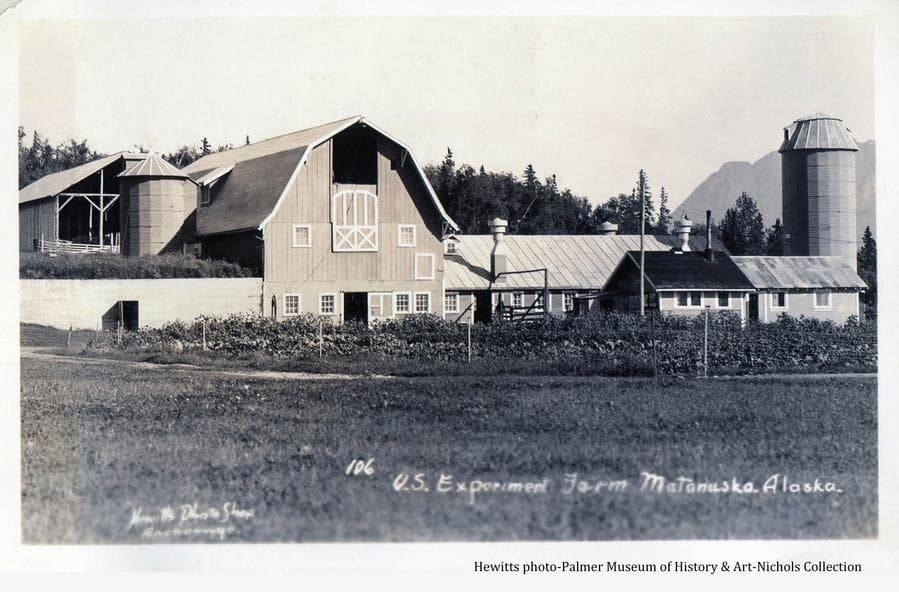 Image shows a grass field in foreground, the barn, silos and associated buildings of the Experiment Farm in middle ground, forest behind and part of Pioneer Peak in background.