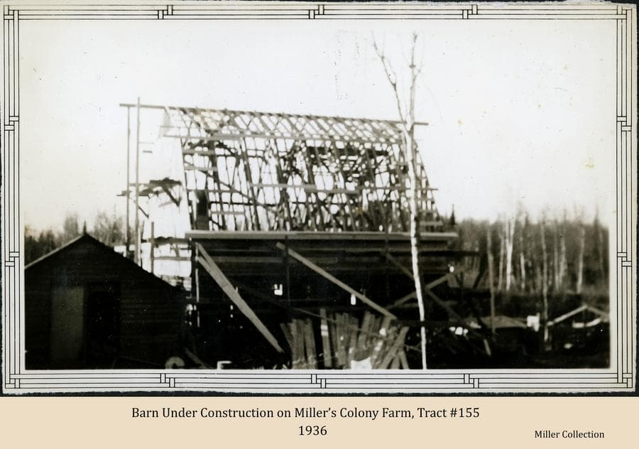Image shows a Colony barn under construction with the bottom portion complete and the roof framed and ready to be covered.  The farm's well house and a stack of lumber are in the foreground.