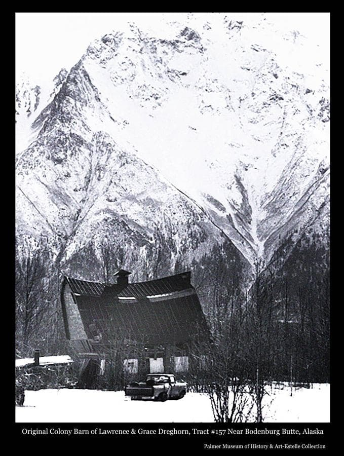 Image is a winter view of a Colony Barn, identified as located on Tract#157 near Bodenburg Butte and having originally belonged to Colonists Lawrence and Grace Dreghorn.  The barn exhibits evidence of early stages of collapse.  A smaller structure, possibly a chicken coop, is apparent at left and a pick-up truck is parked in foreground.  Pioneer Peak is the backdrop.
