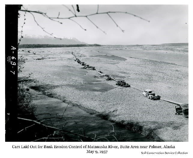 """Image is a low oblique view of several junk cars laid out in a curved line on a river gravel bar with logs between them. Extensive gravel expanse and the river channel are evident with mountains in background. Caption: """"Butte area, shows cars as laid out for streambank control."""""""