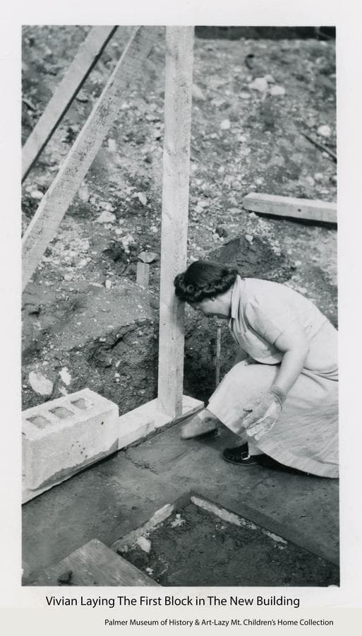 Image shows a woman, identified as Vivian, laying down mortar to receive the first concrete block in construction of the basement of the new permanent building for the Home.