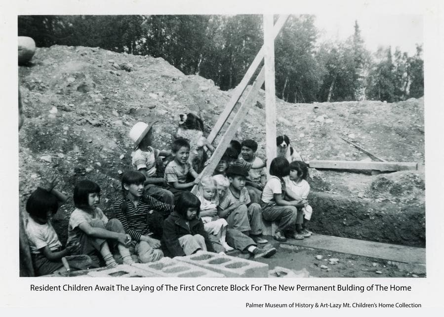 Image shows a group of resident children waiting for the ceremony to lay the first concrete block in construction of the basement of the new permanent building for the Home.