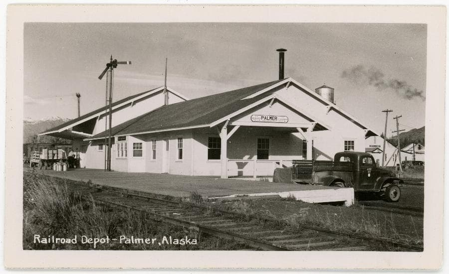 Image shows the Palmer railroad depot viewed from the southwest corner, including railroad tracks in foreground, an ARRC pickup truck, a railroad semaphore signal, part of the Palmer water tower, power poles, and smoke from the powerhouse. On the dock is a man moving a freight cart, a loaded freight cart, and several milk cans. Rail cars are on the siding behind the depot and mountains are partly visible in background.