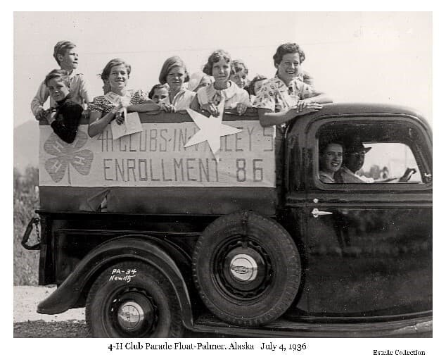 """Image shows a side view of a pickup truck with several children standing in the back facing the camera. One girl holds a large paper star. A sign on the side of the truck shows the 4-H clover leaf symbol and text: """"4H CLUBS-IN-VALLEYS: 5, ENROLLMENT: 85"""". A spare tire is prominently mounted on the side of the truck. The driver, identified as Howard Estelle, and passenger, identified as Ruth DeArmond, are visible in the truck cab."""