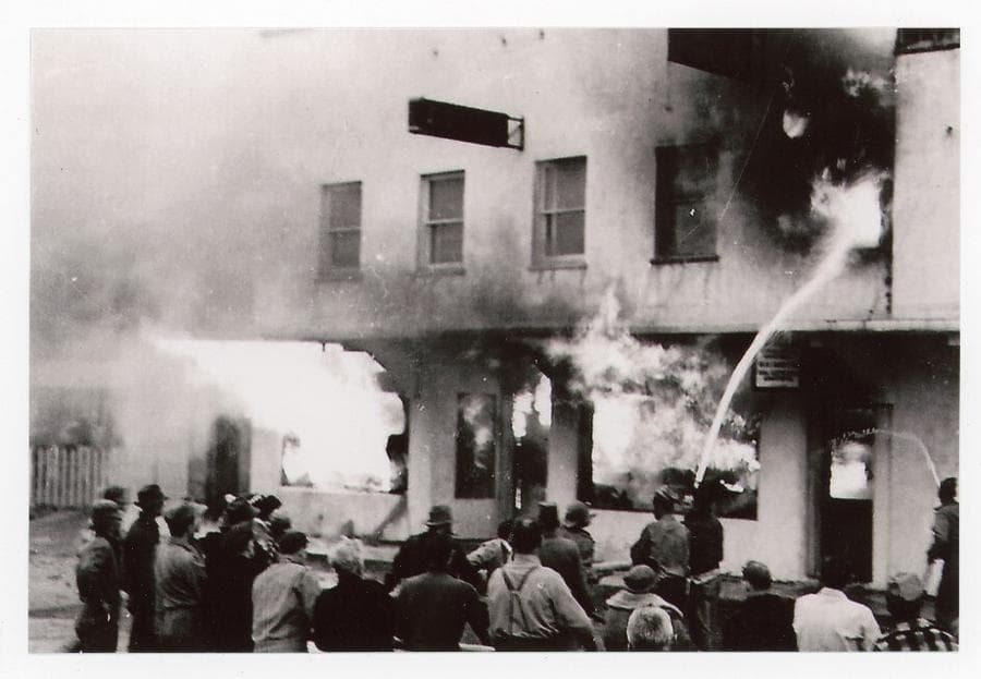 Image shows a crowd of people in foreground facing a burning building, flames & smoke exit doors and windows while two men hose water on the flames.